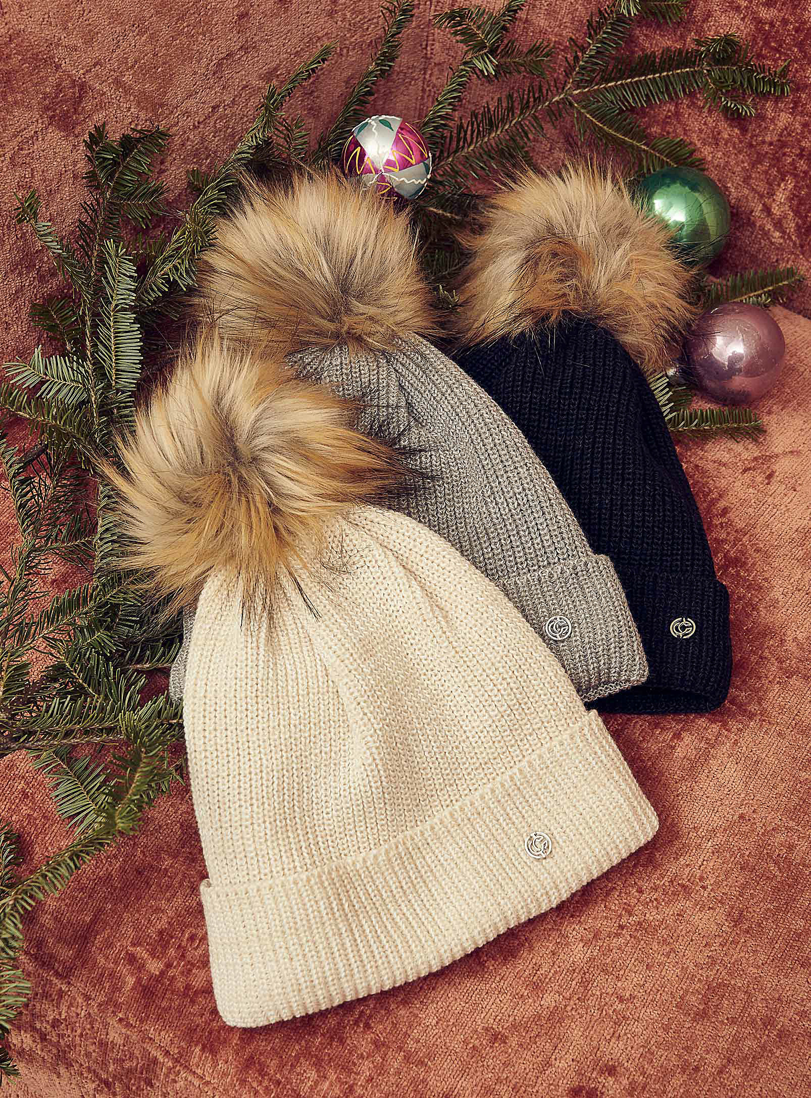 Three knit hats with fluffy pom poms on a carpet