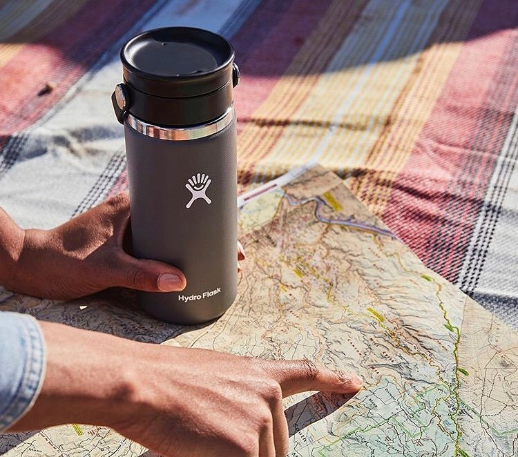 A person holding a travel coffee mug while looking a map