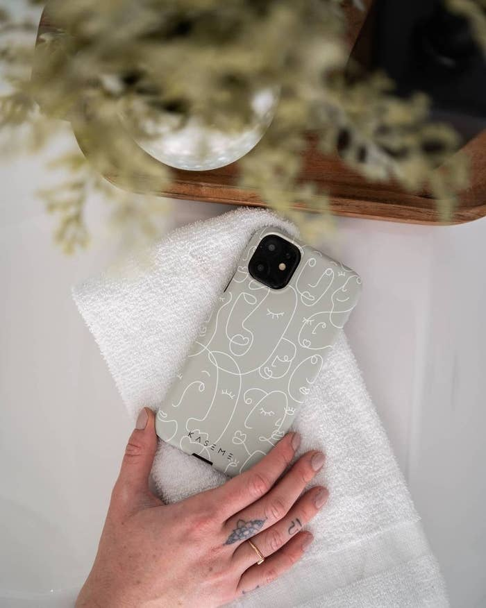 An iPhone on a table with a hard case that has an illustrated face print on it