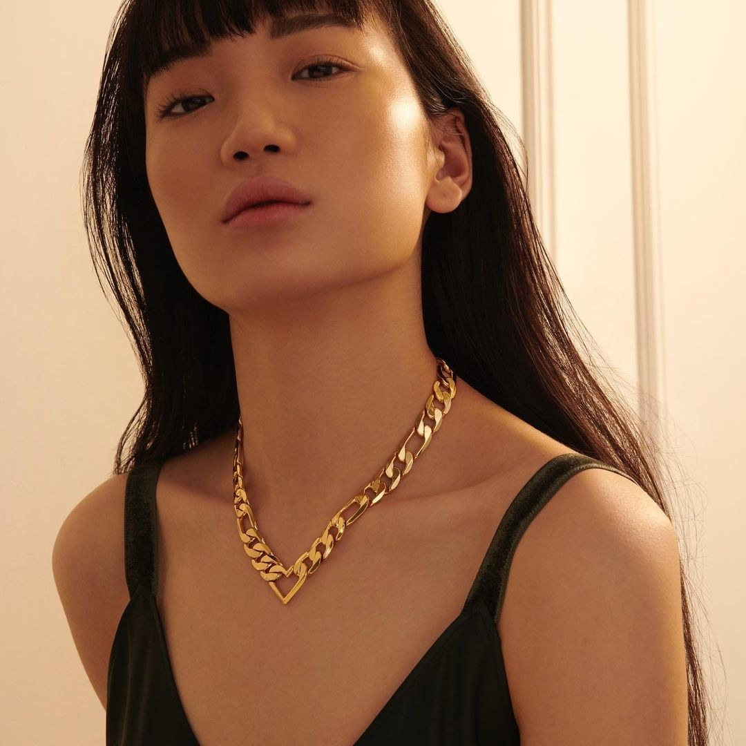 A person wearing a gold chain necklace with a heart pendant at the center