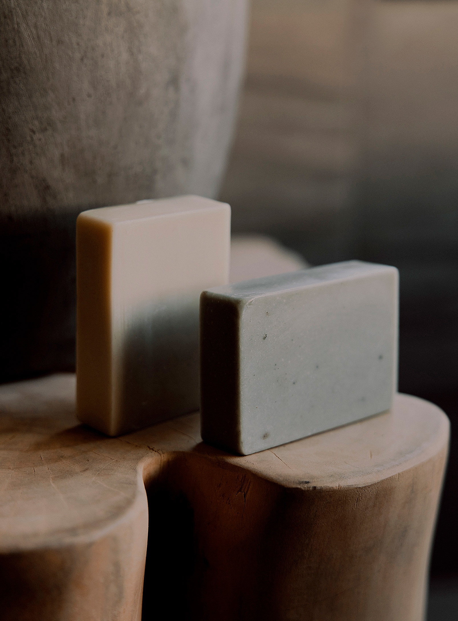Two bars of soap on a wooden stool