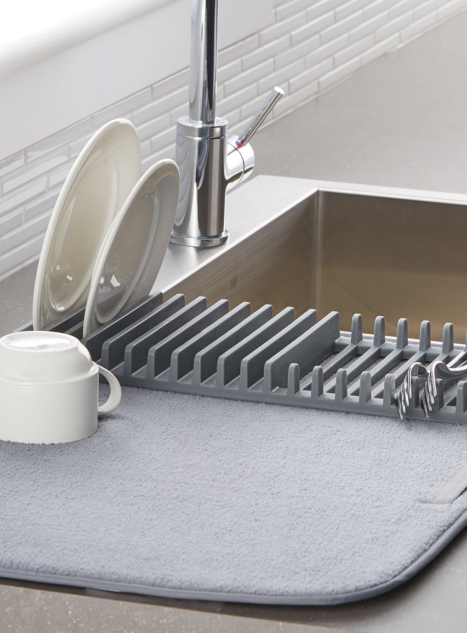 A silicone dish rack attached to a large micofibre mat that has a cup, plates and a couple of forks drying on it