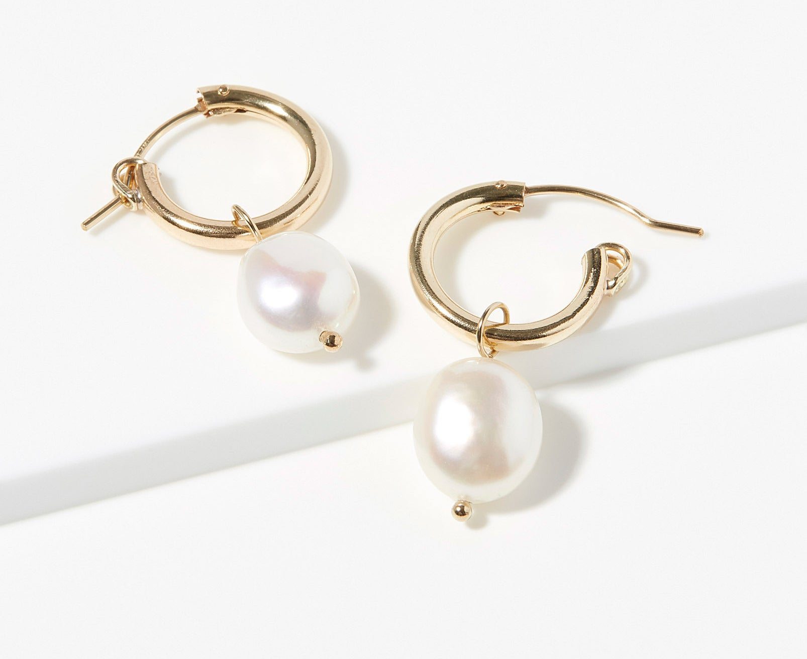 A pair of tiny hoop earrings with a pearl hanging from the bottom