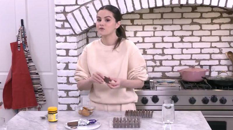 Selena in her kitchen, holding up a Tim Tam