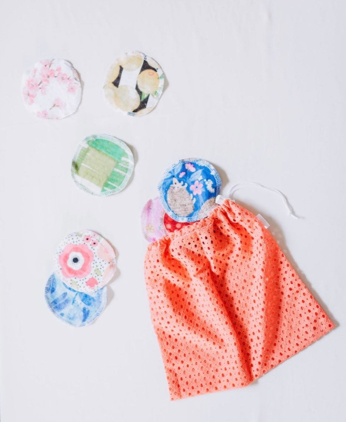 Six cotton rounds next to a small drawstring bag