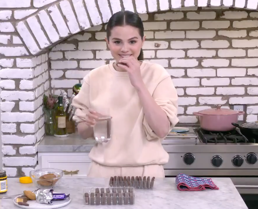Selena in her kitchen, smiling at the camera; she is holding a Tim Tam and a glass of water