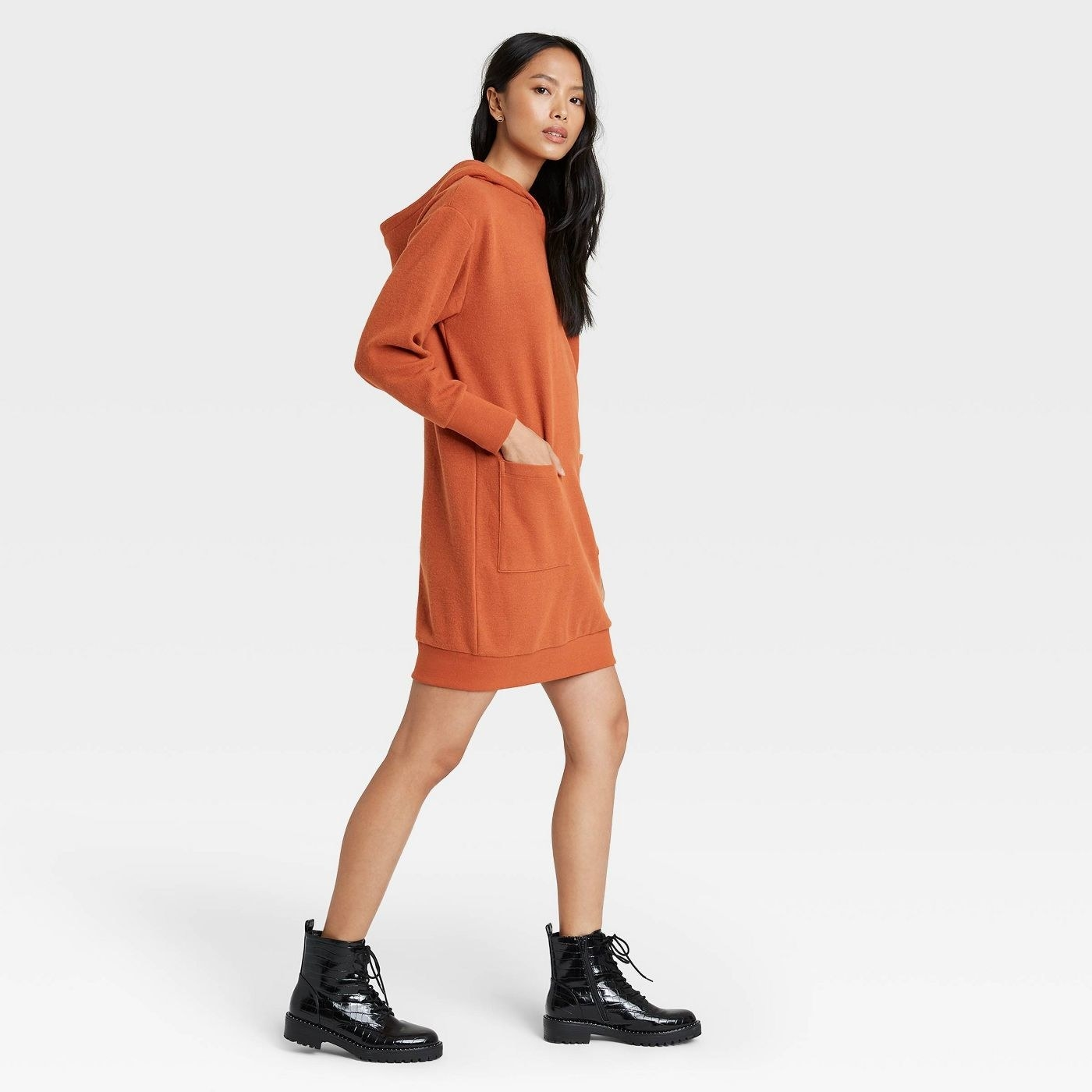 a model wearing the hoodie dress in the color brown which looks like burnt orange