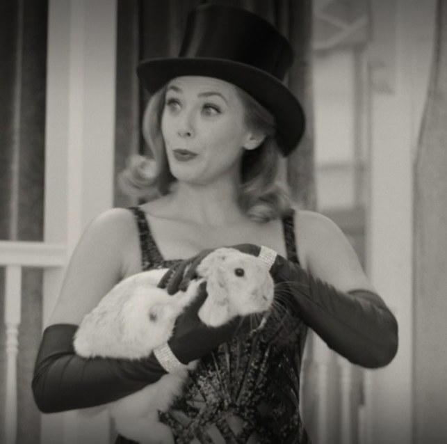 Wanda wears a tophat and holds a rabbit