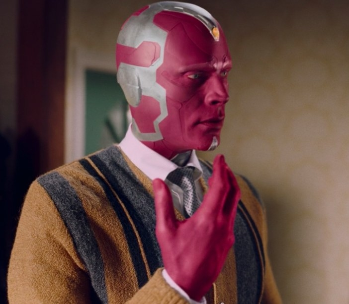 Vision wears a cardigan and holds up one hand