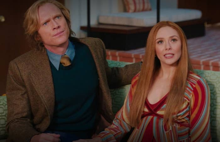 Wanda and Vision wearing '70s clothes sit on a couch looking uncertain