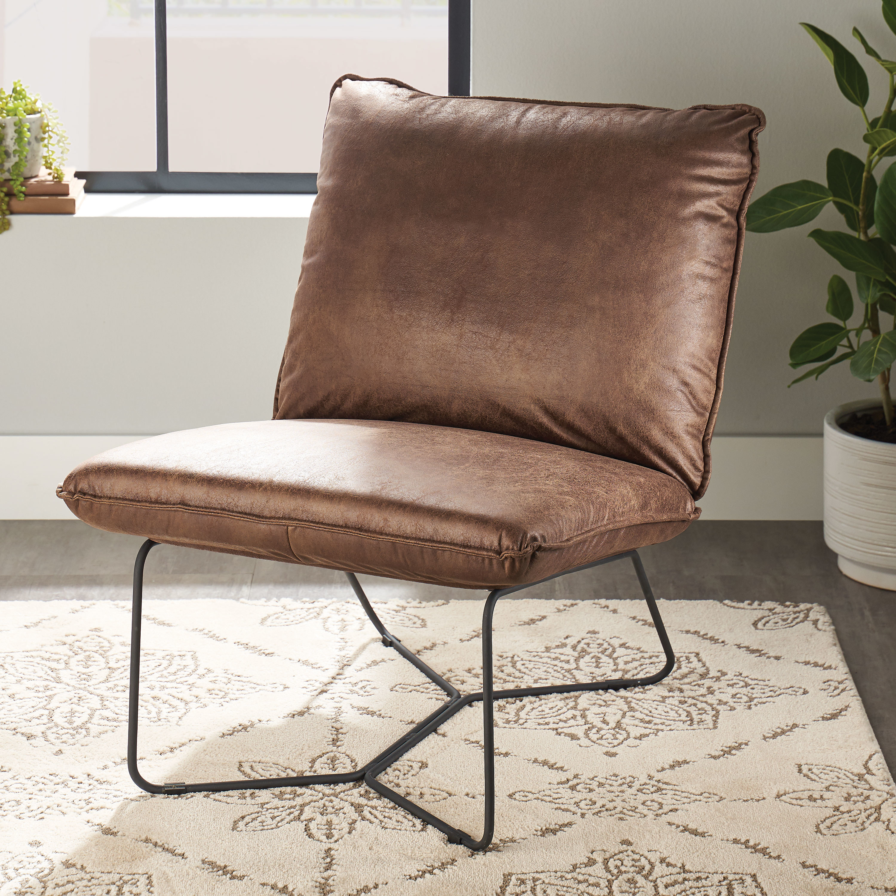 a brown leather pillow chair with black legs