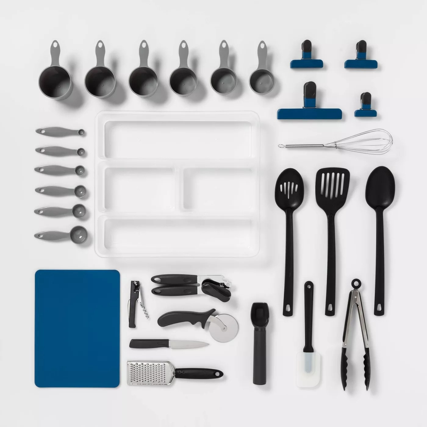 The measuring cups, cooking utensils, a cutting board, chip clips, a corkscrew, an ice cream scoop, a cheese grater, a can opener, and an organizer