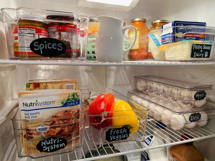 A reviewer's photo of their fridge organized with the six clear containers