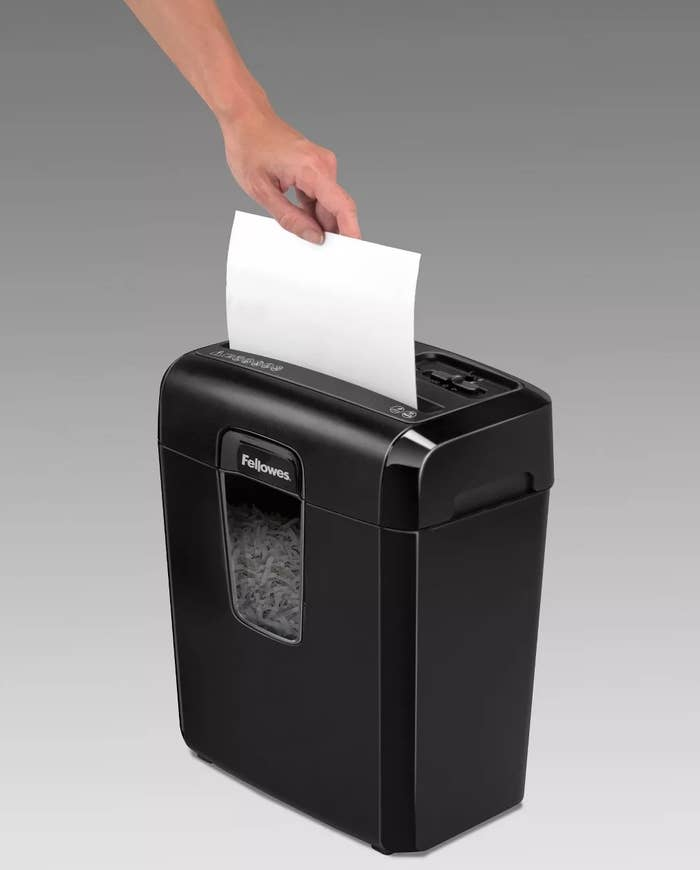 A model inserting a piece of paper into the Fellowes paper shredder