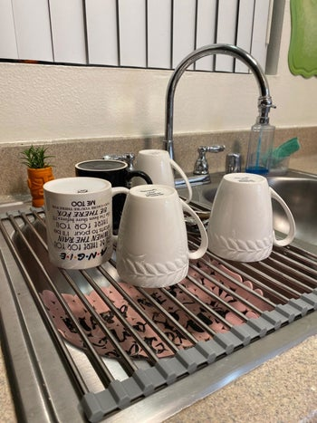 A reviewer's photo of the stainless steel rack holding five mugs
