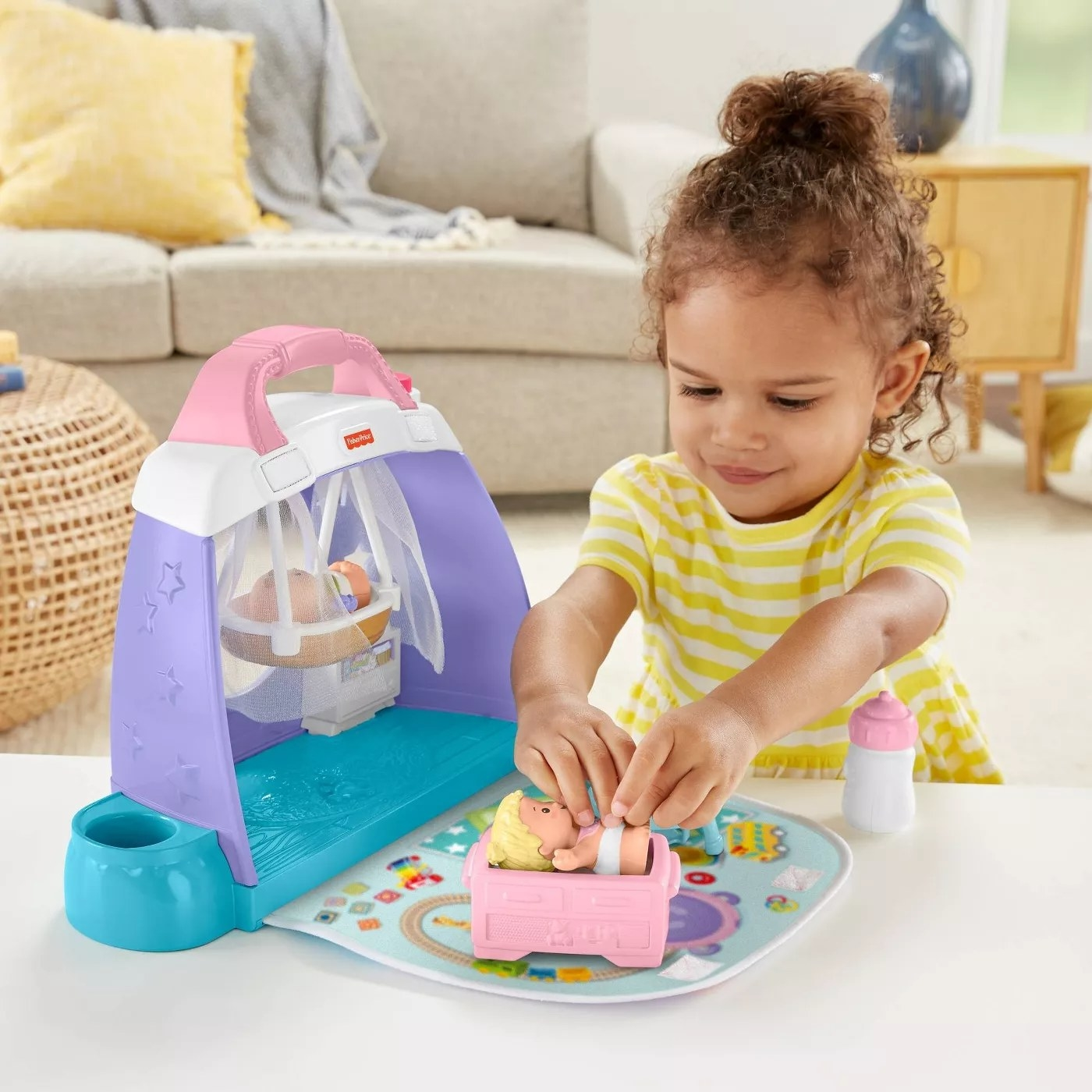 A child playing with one of the babies in the nursery playset