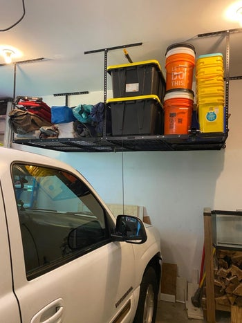 A reviewer's photo of the black shelving unit holding various buckets, storage containers, and camping equipment