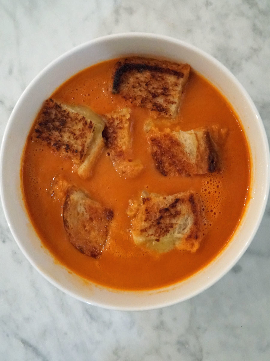 A bowl of tomato soup with mini grilled cheese croutons.