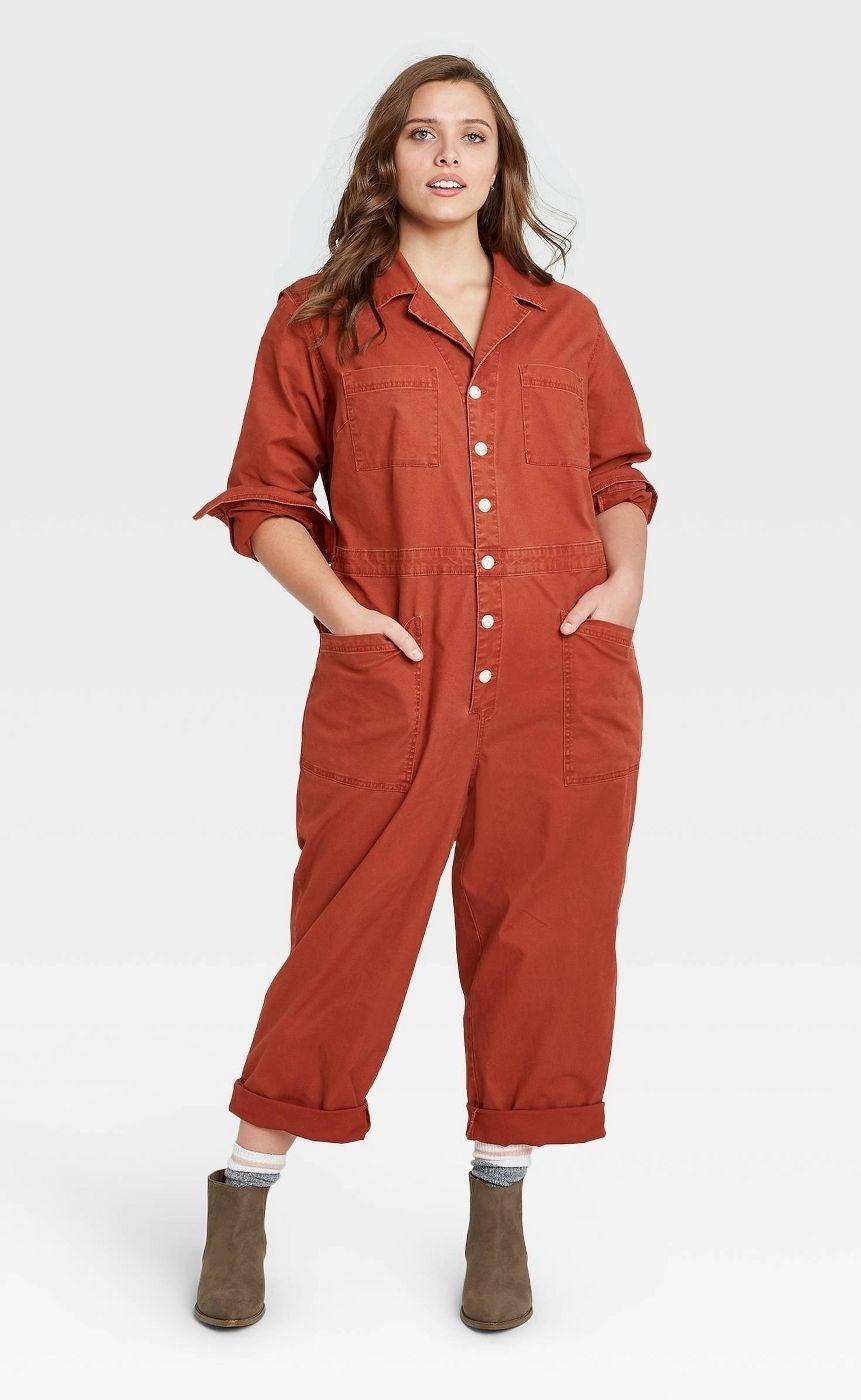 Model wears red long-sleeve collared boilersuit with brown booties