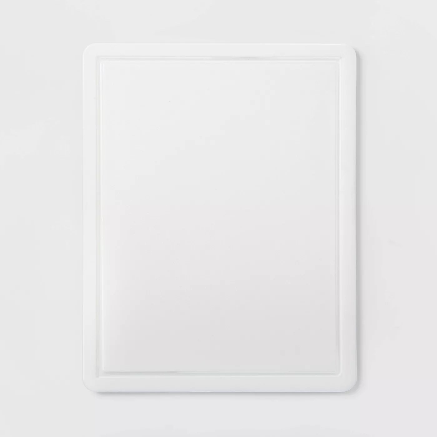The white, grooved, nonslip cutting board