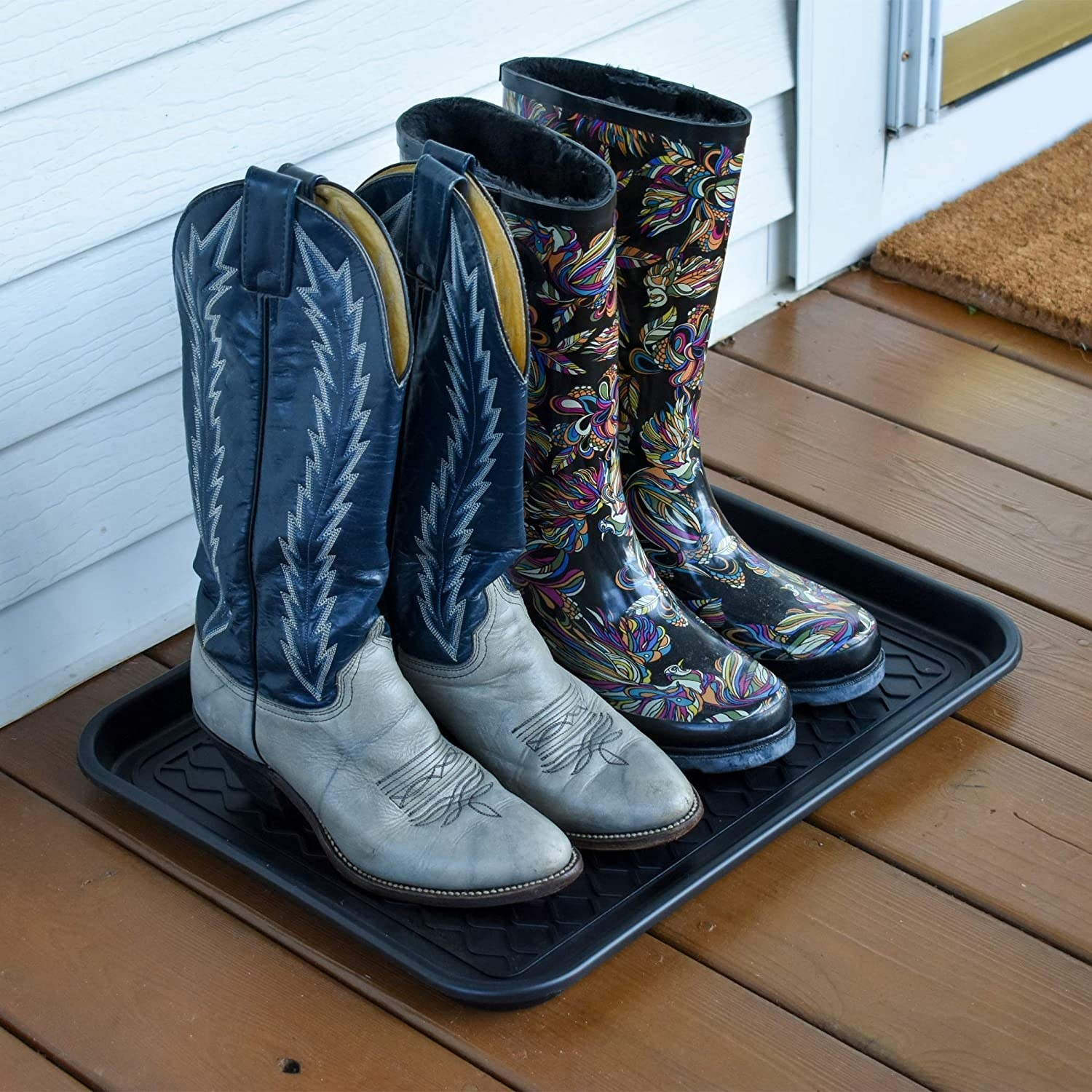 Two pairs of boots on a rubber tray on the porch