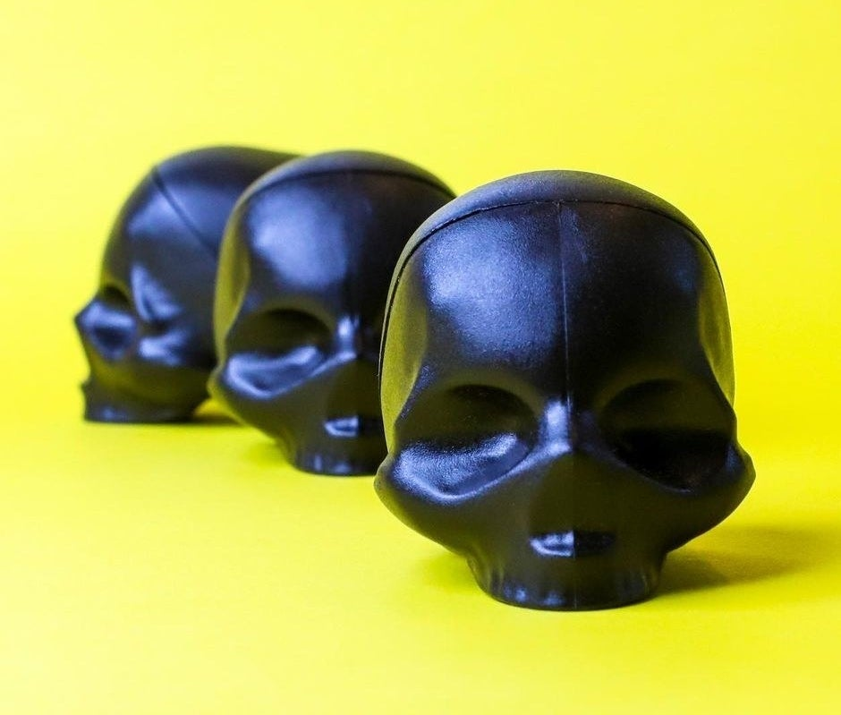 A trio of skull-shaped lip balms on a bright background