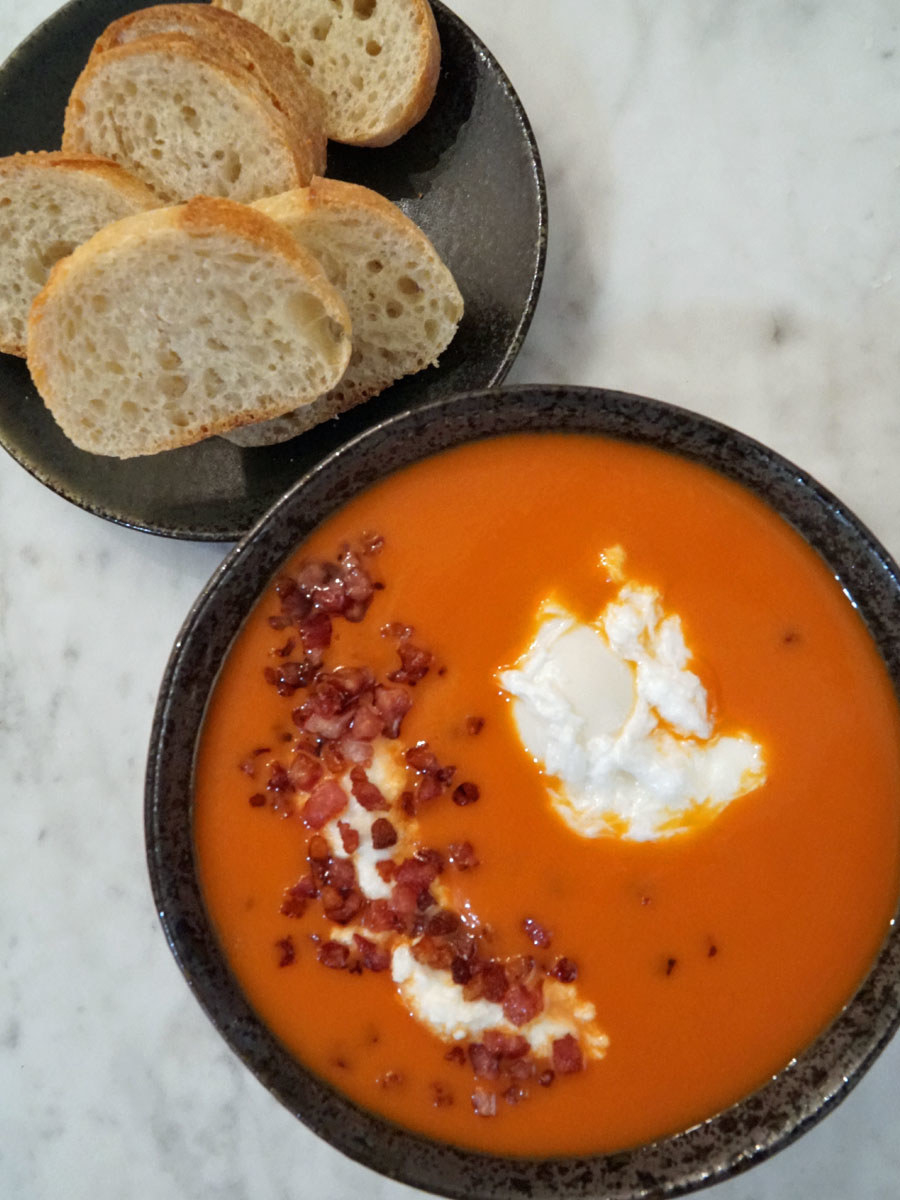 A bowl of tomato soup with poached egg, ricotta, and pancetta.