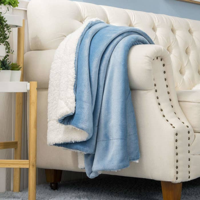 A blue faux fur blanket draped on a beige couch.