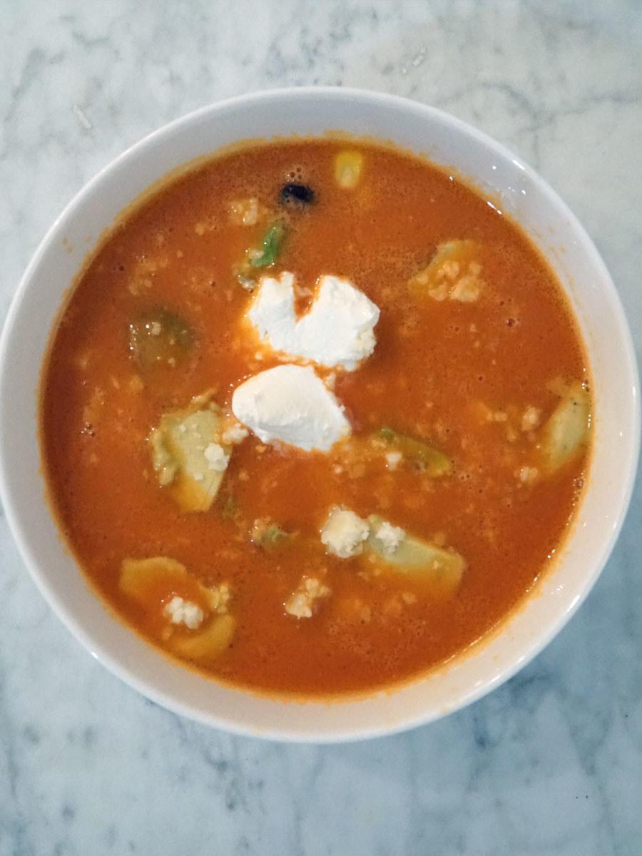 A bowl of taco tomato soup with sour cream and avocado.