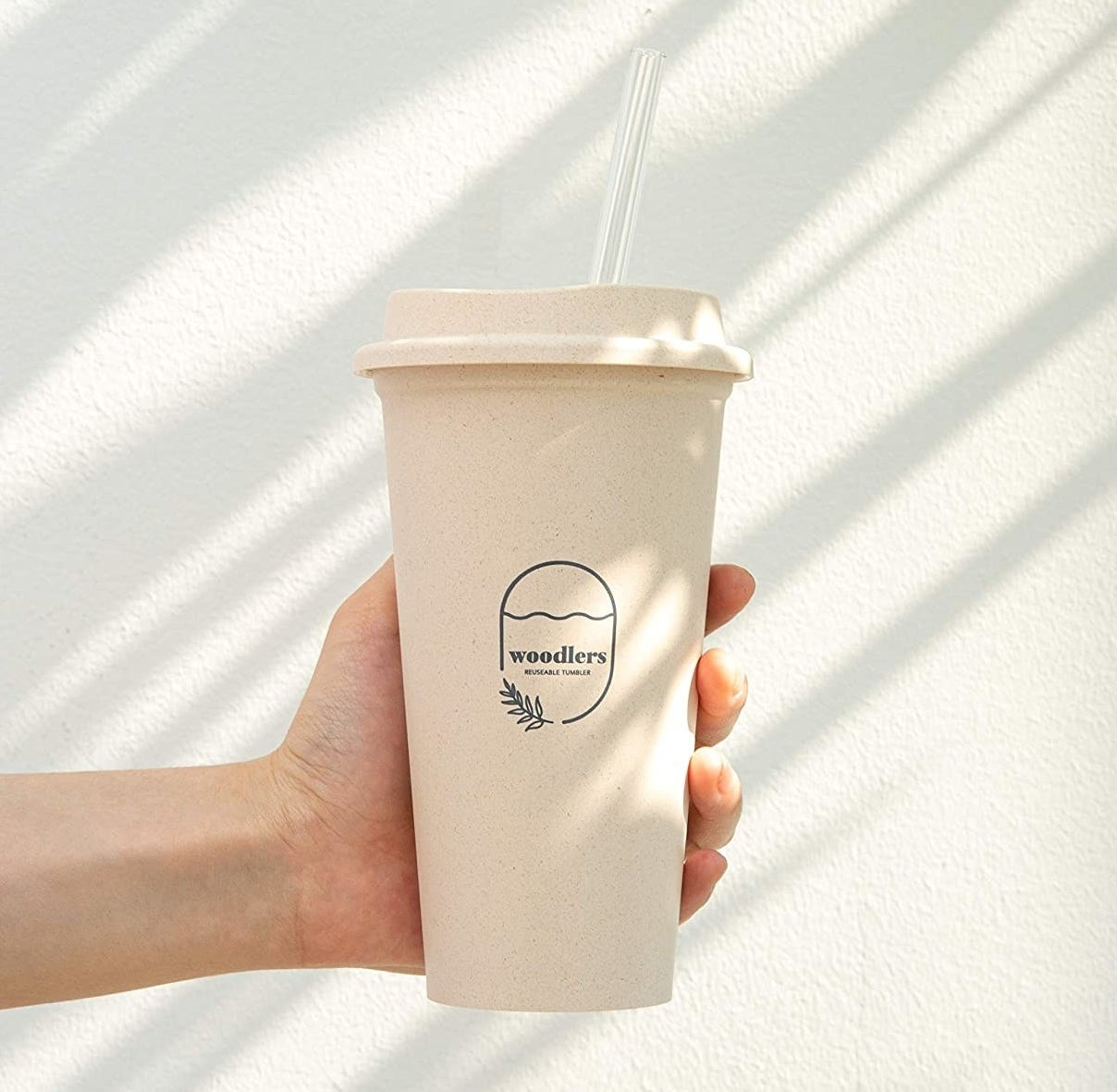 hand holding the ivory travel cup