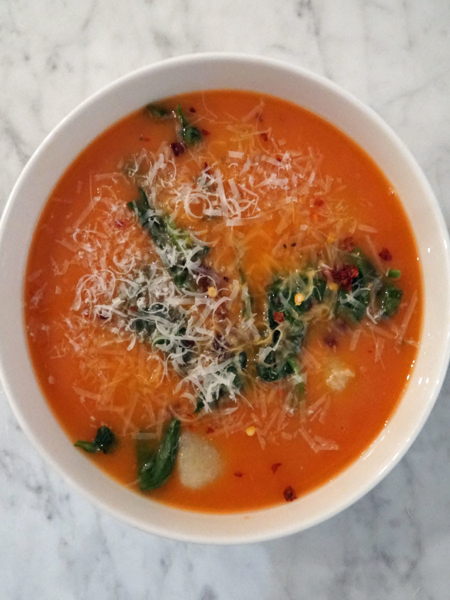 A bowl of tomato gnocchi soup with spinach.