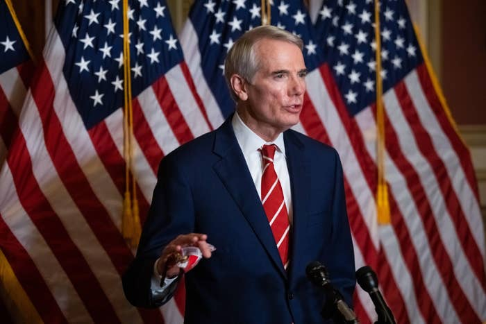 Rob Portman stands in front of some American flags