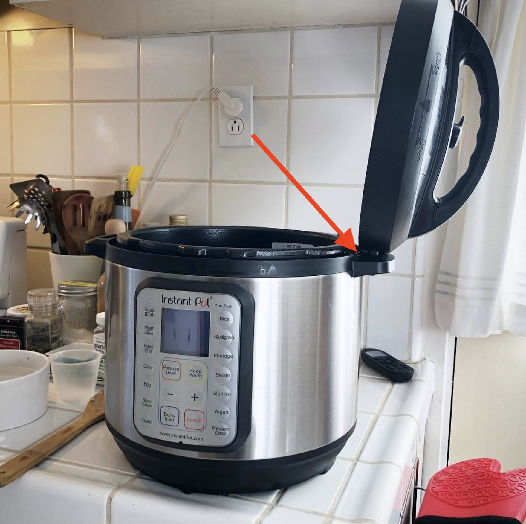 The lid of an Instant Pot balancing on the Instant Pot's side handle