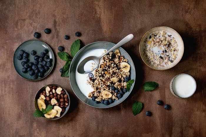A bowl of cereal surrounded by toppings like dried fruit and berries.