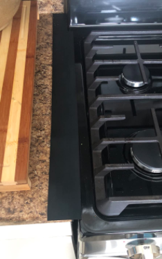close up of the black strip on the edge of the stovetop that blends in with the black oven