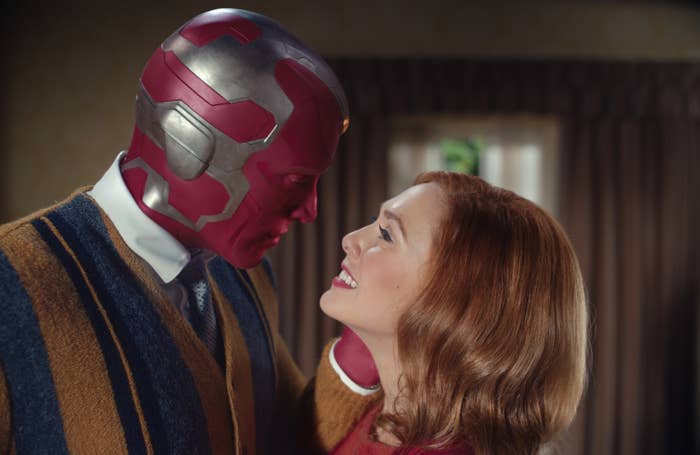 """Paul Bettany as Vision and Elizabeth Olsen as Wanda lovingly stare into each other's eyes during a scene in """"WandaVision"""""""