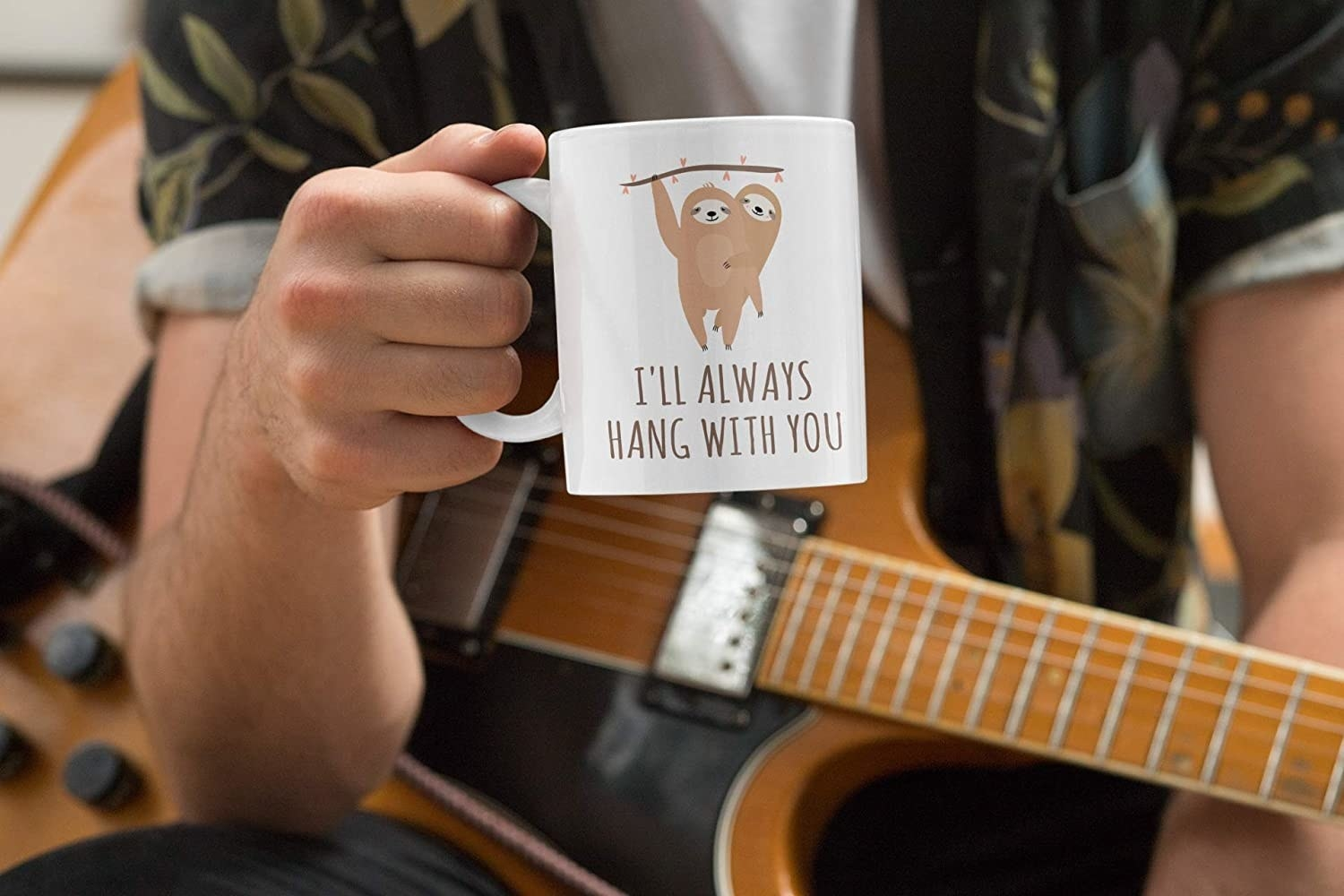 person holding a mug with sloth drawings that says I'll always hang with you