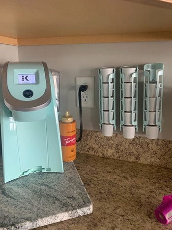 A reviewer's photo of the blue dispensers mounted next to their coffee maker