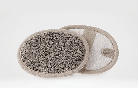 Oval skin cleaning mitt with scrubbing side and strap for hand, including a loop for hanging storage