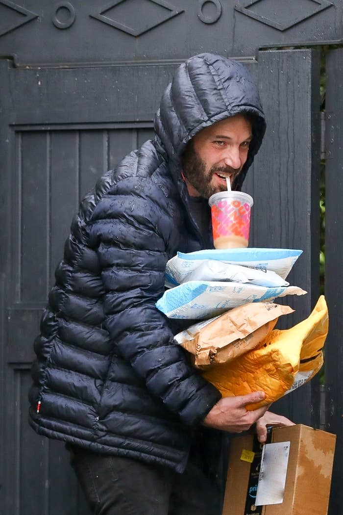 Ben Affleck smiles as he sips on his iced coffee and balances the packages