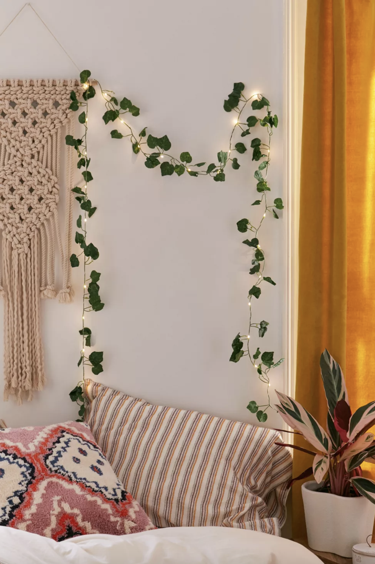 The faux ivy string lights hanging on a wall in a cozy-looking room