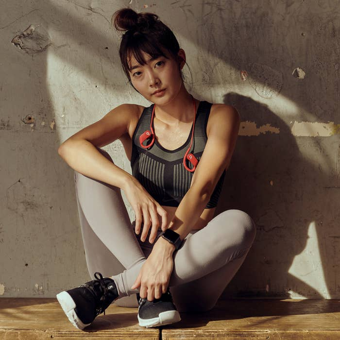 A model in athletic clothes wearing the headphones