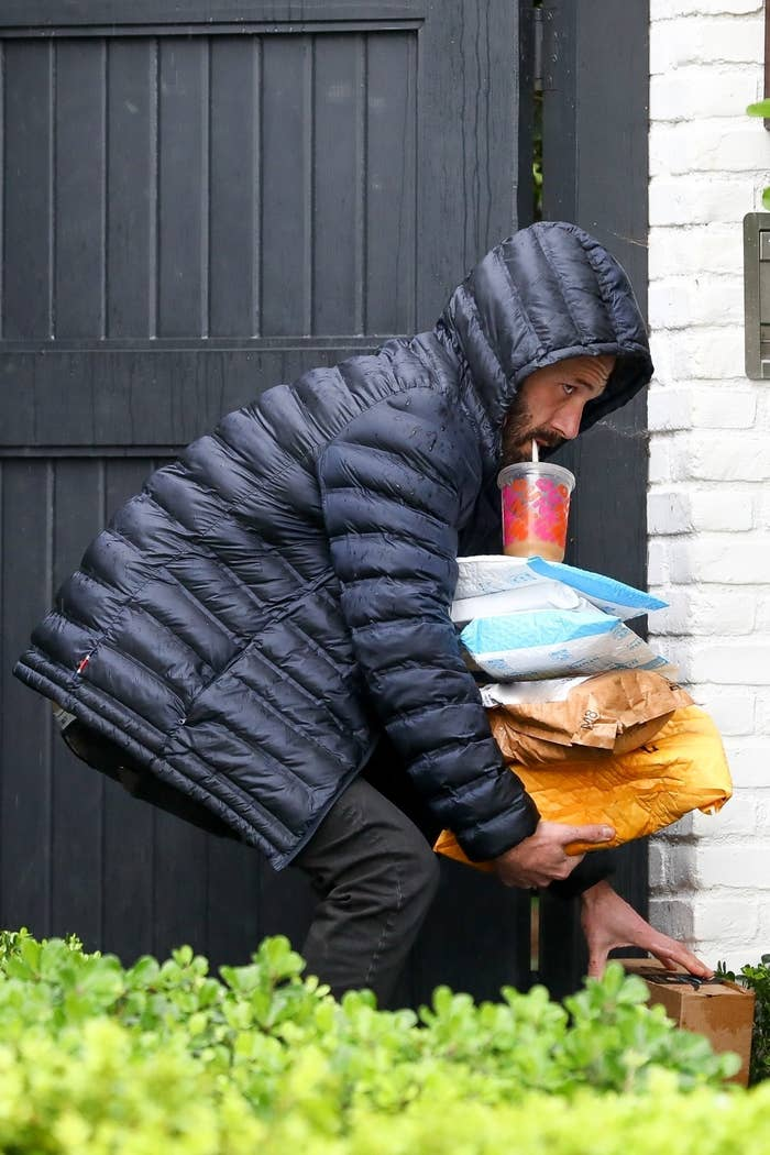 Ben Affleck, dressed in a puffy jacket with the hood up, hunches over to pick up a package with one hand as he balances several other packages with a large iced coffee sitting on top with his other arm