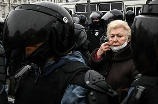 An elderly woman surrounded by police officers at a pro-Democracy rally in Russia.
