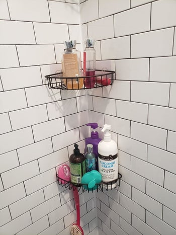 A reviewer's photo of the black caddies holding body wash, loofahs, and other bath products