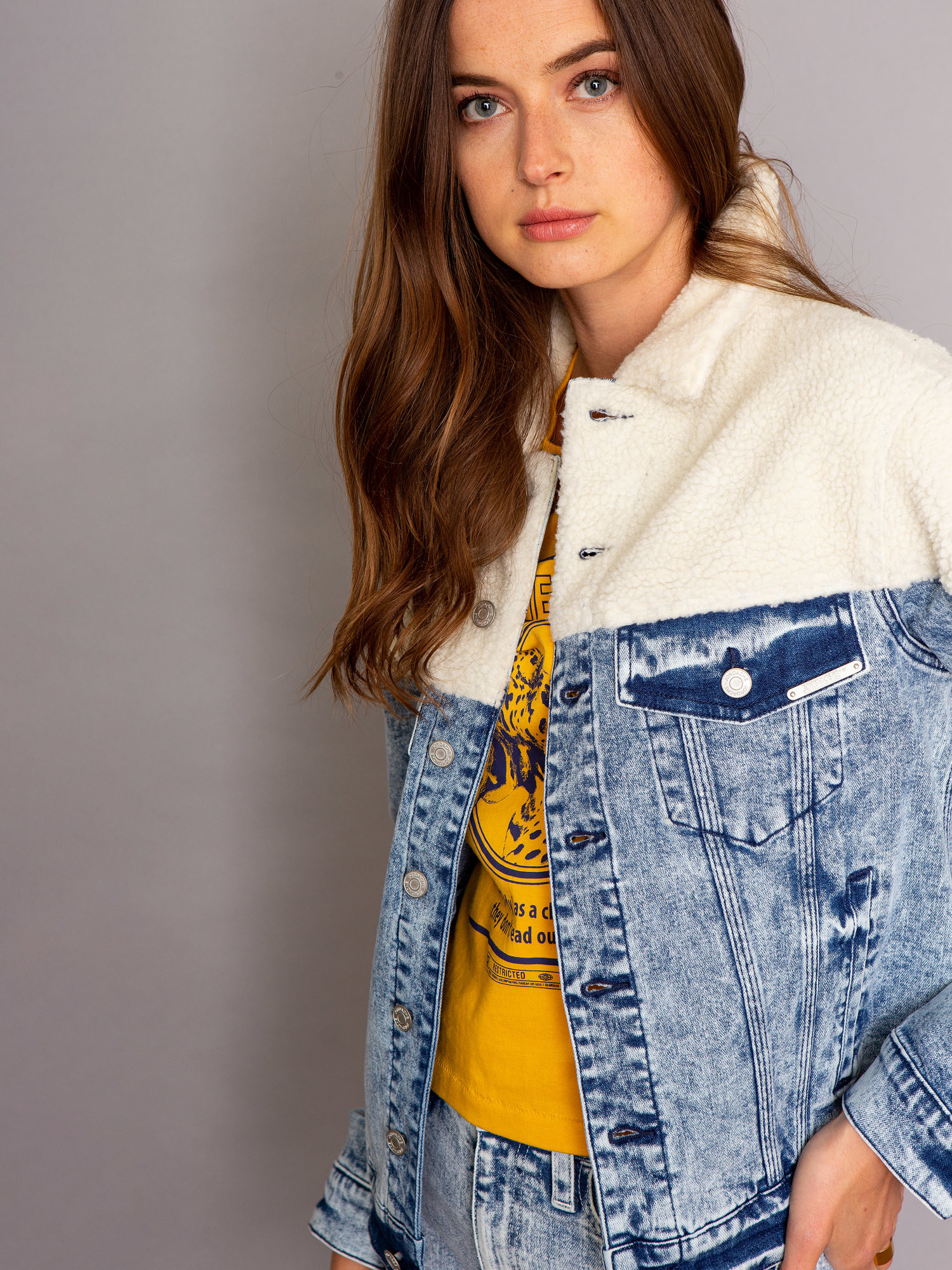 a model in a denim jacket with the top portion made of sherpa