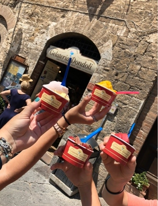 Four hands hold up red to-go cups of colorful gelato with spoons sticking out the scoops, all in front of the storefront made of old stone