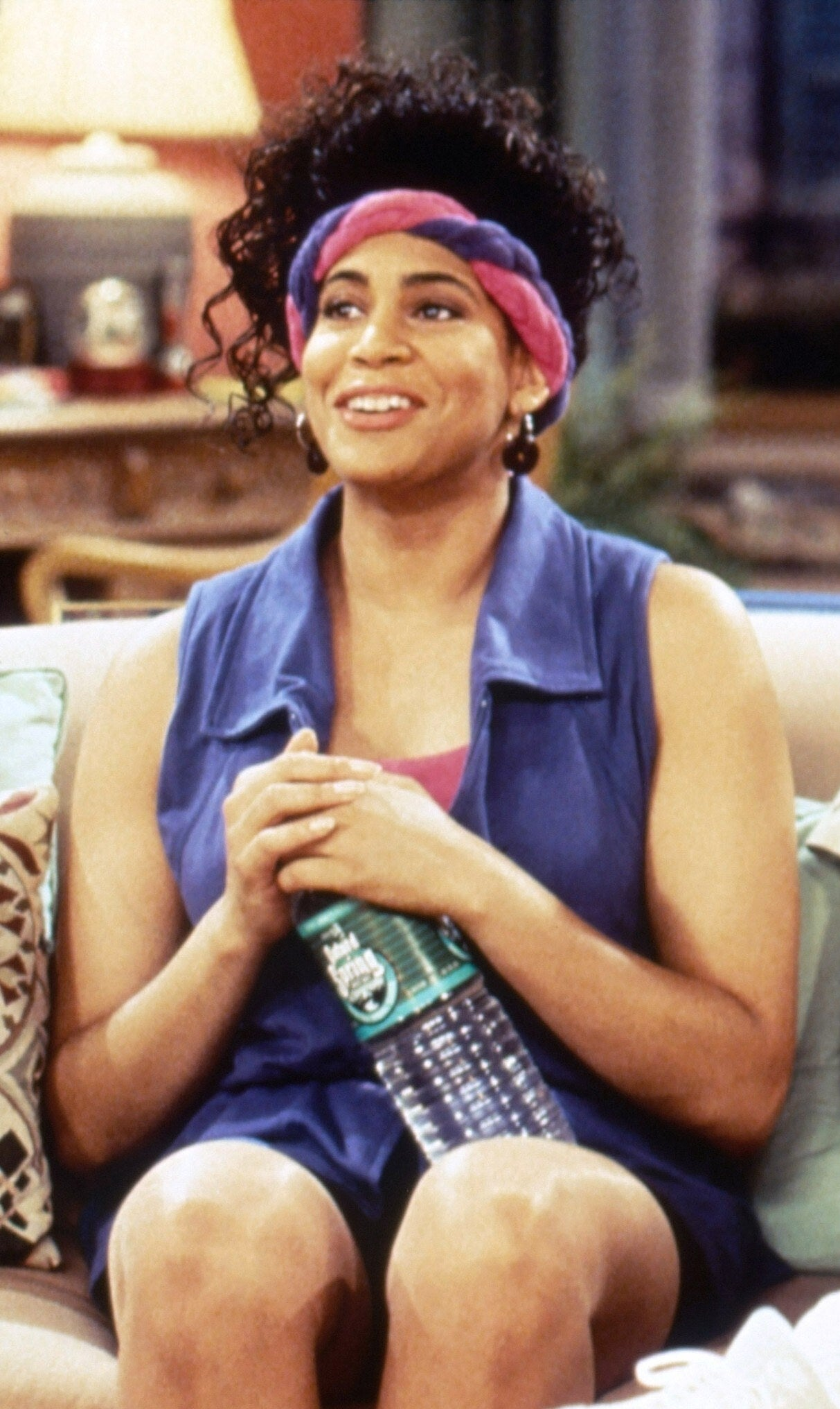 Kim Coles is sitting on a couch in the living room while holding a bottle of Poland Spring water, as she gazes outward