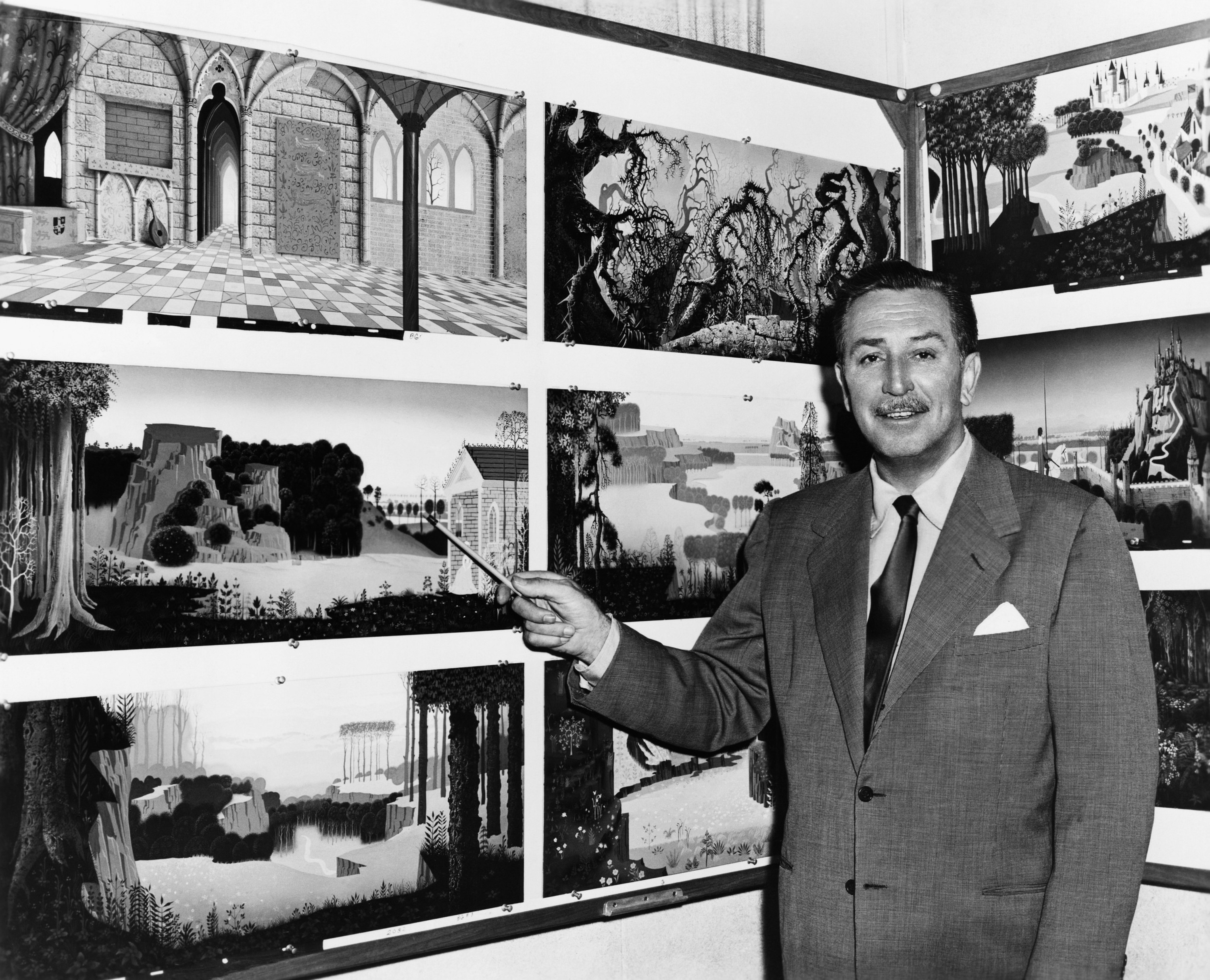 A photo of Walt Disney sharing background paintings from Sleeping Beauty