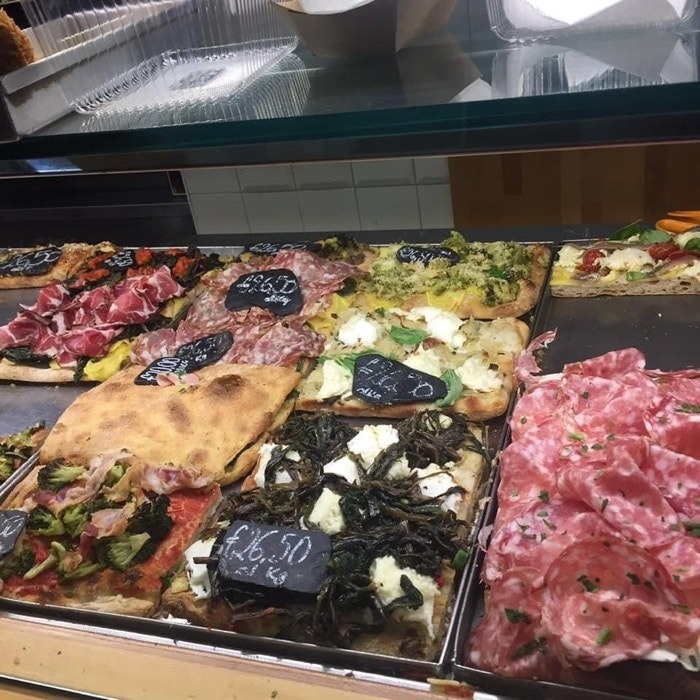 A display case full of different kinds of pizza by the slice